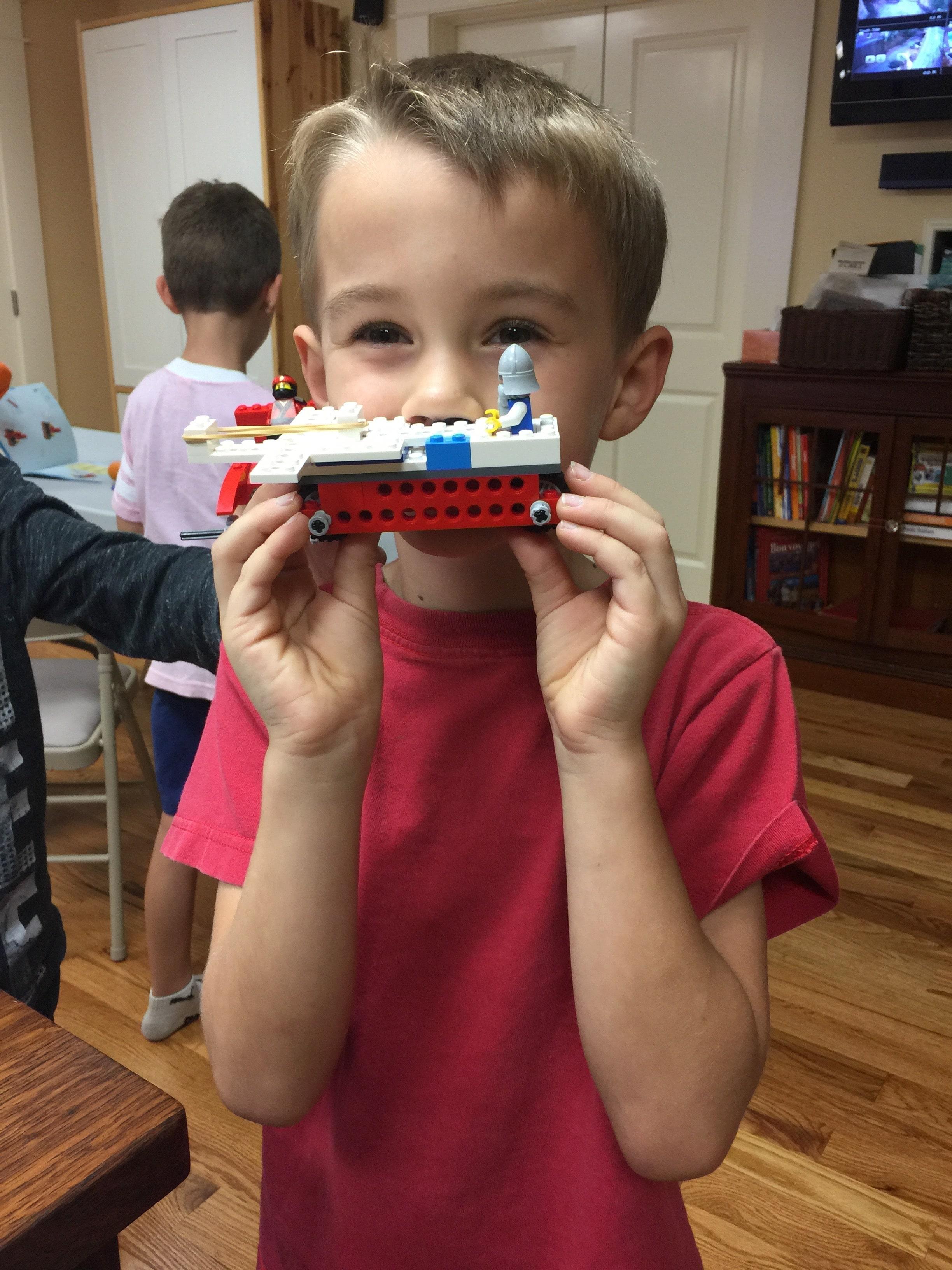 Boy in Atlanta class with Lego Robotics project
